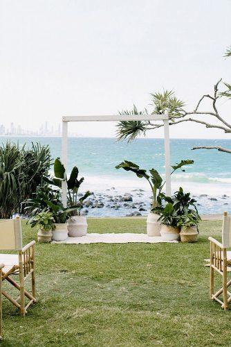 wedding altar decoration white arch with straight corners on the grass by the sea is decorated with tropical plants heart and colour via instagram