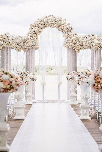 wedding altar decoration white arches are decorated with many colors and a light white cloth anna kozdurova via instagram