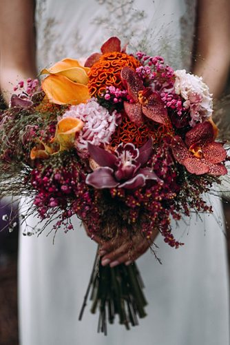 bridal bouquet with dark orchids and orange flowers lorena erre photography