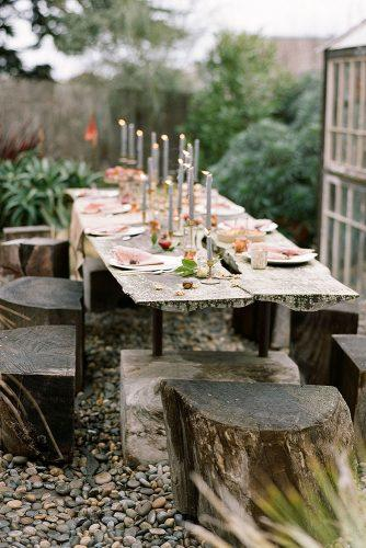 rustic backyard wedding decoration rough wooden table with candles and hemps instead of chairs josh gruetzmacher photography