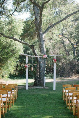rustic backyard wedding simple wooden arch decorated with flowers and suspended details swoon by katie
