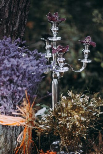 silver candlestick with orchids and dried flowers lorena erre photography