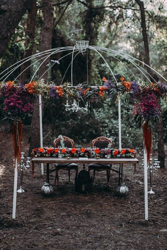 white arbor decorated with flowers dark table and chairs with patterns lorena erre photography