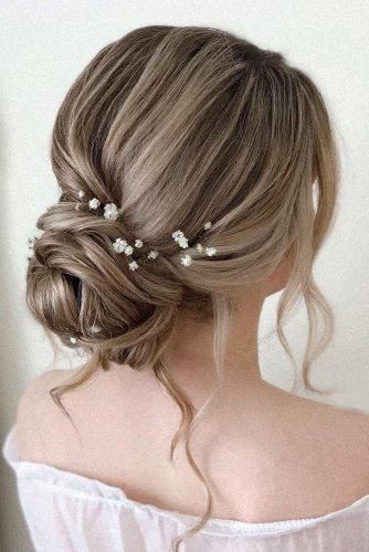rustic wedding hairstyles elegant low bun with loose curls and baby breath pearly.hairstylist