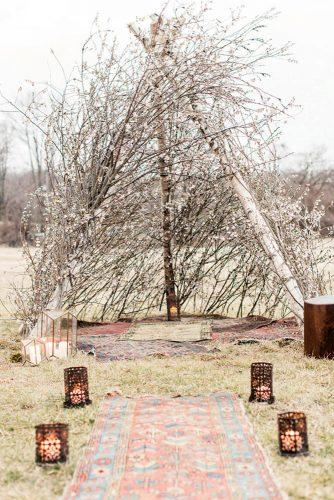 bohemian wedding ideas boho wooden arch with branches with carpet and lanterns and aisle lauren fair photography