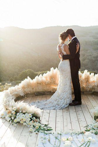 bohemian wedding ideas groom and bride on the wedding altar decorated with pampas grass carlie statsky