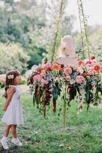 bohemian wedding ideas suspended cake stand decorated with flowers caitlinjoycephotography via instagram