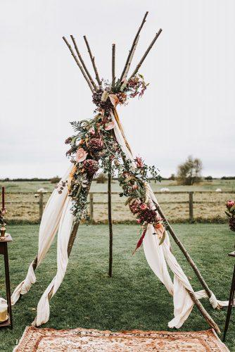 bohemian wedding ideas wooden nacked teepee altar decorated with flowers darina stoda photography