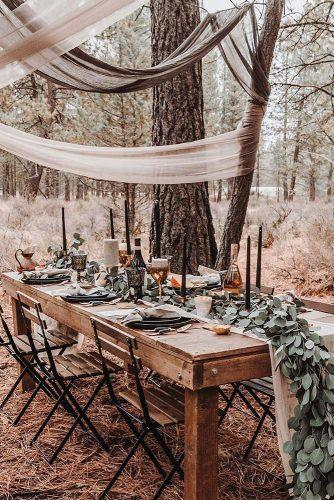 bohemian wedding ideas woodland reception with cloth decorations greenery and candles k.gabrielle.photography