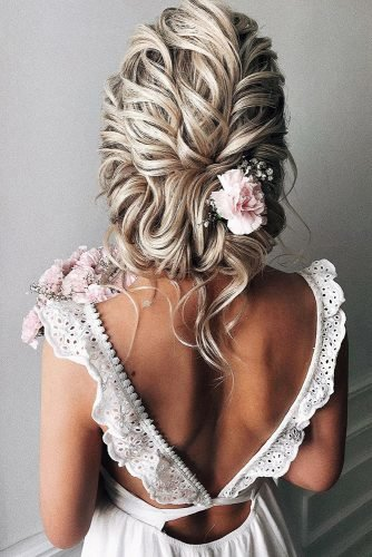rustic wedding hairstyles low slightly messy textured updo with pink roses alexandra_poslavskaya