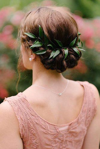 rustic wedding hairstyles low updo with green leaves morning light by michelle landreau