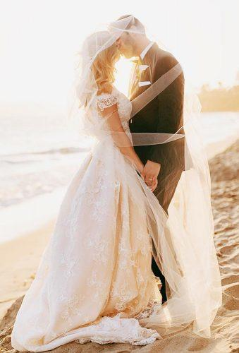 couple poses under veil on the beach chardphoto