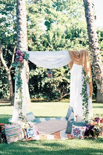 bohemian wedding theme ceremony altar with white tablecloth and greenery carolly photography