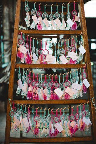 bohemian wedding theme escort card display with colorful dream catchers izzy hudgins photography