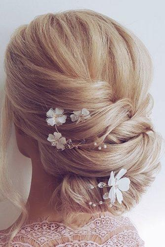 boho wedding hairstyles blonde low bun with white flowers hairbyhannahtaylor