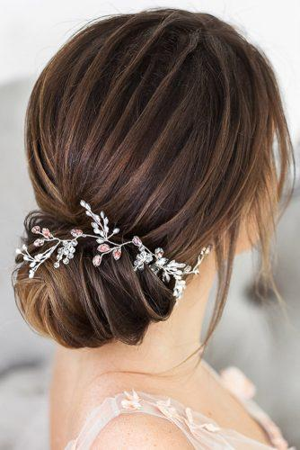 classical wedding hairstyles elegant low bun with elegant accessories with leaves and pink flowers elstilespb