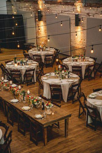 wedding loft décor reception with round tables rlowers and light bulbs happily ever after
