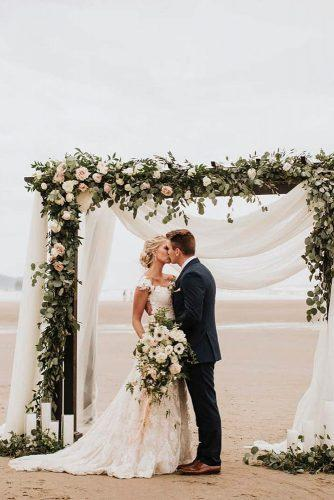 wedding ceremony decorations on beach with white cloth and greenery candles victoriacarlsonphoto