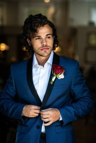 arabic wedding grooms look blue suit red boutonniere photograph