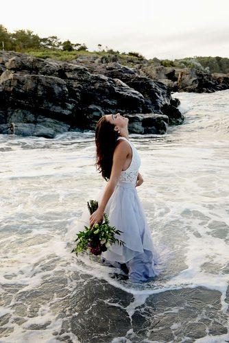 beach photoshoot beach styled shoot bride in a white dress is standing in the sea alexi