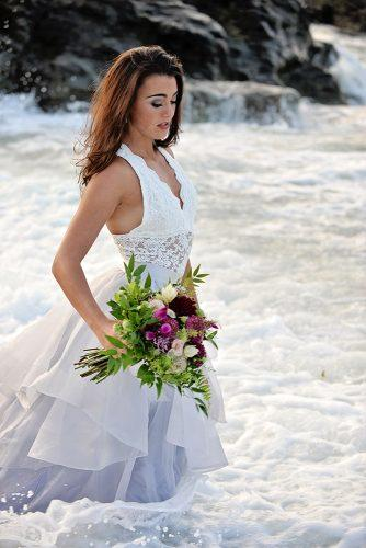 beach photoshoot beach styled shoot bride in a white dress with bouquet elegant makeup is standing in the sea alexi