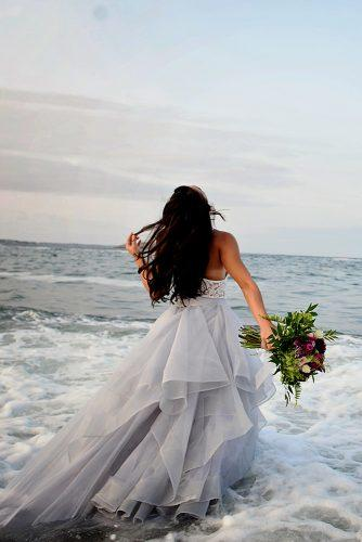 beach photoshoot beach styled shoot bride in a white dress with bouquet is standing in the sea alexi