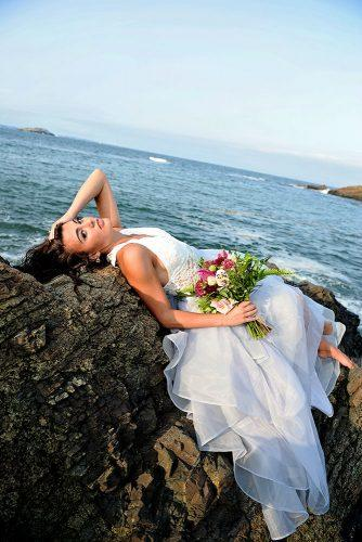 beach photoshoot beach styled shoot bride with a bouquet lies on the rocks against the sea alexi