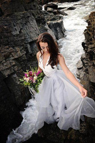 beach photoshoot beach styled shoot bride with loose medium hair on the rocks above the sea alexi