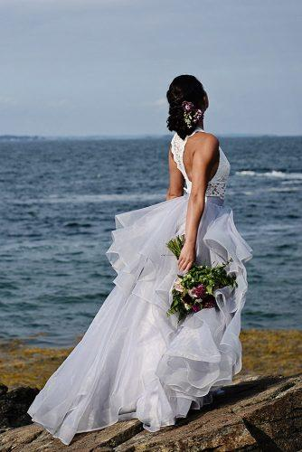 beach photoshoot beach styled shoot bride with wedding bouquet flower updo in a lush white dress on the rocks against the sea alexi