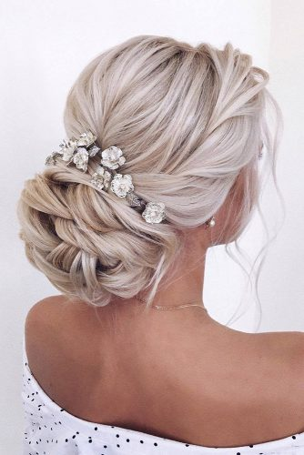 wedding hairstyles 2019 low volume bun on blonde hair with accessories american_salon