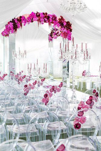 wedding trends 2019 ceremony under white tent with clean actylic chairs and arch with crimson orchid flowers katiebeverleyphoto