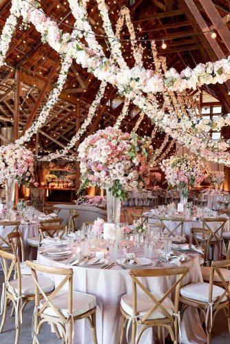 wedding trends 2019 elegant wedding reception in barn with tall centrpieces pale pink flower handing garlang larissaclevelandphoto