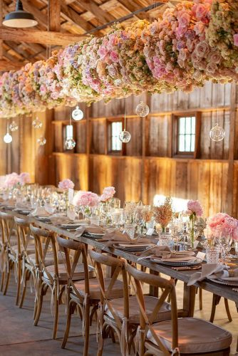 wedding trends 2019 long table in barn with suspended flowers and glass decor eddiezaratsian
