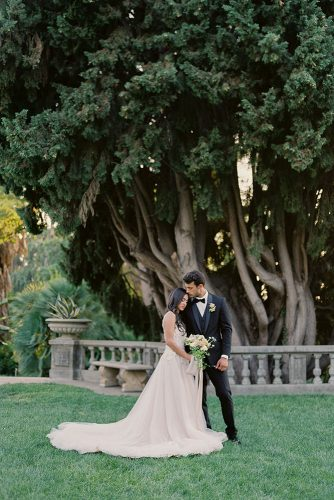 besame wedding styled shoot a bride in a white dress with a train and a bouquet of the groom in a black suit among tall trees carrie king photographer