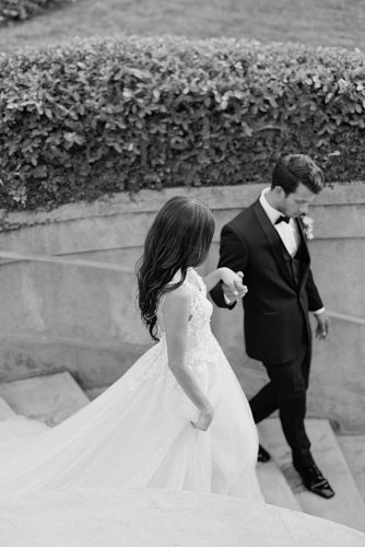 besame wedding styled shoot black white photography the groom leads the bride down the steps carrie king photographer