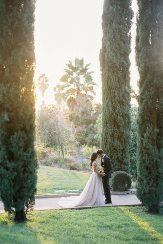 besame wedding styled shoot bride in a dress with a train and the groom among the tall cypress trees carrie king photographer