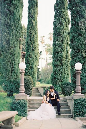 besame wedding styled shoot bride in a dress with a train and the groom in front of sitting on a stone stairs carrie king photographer