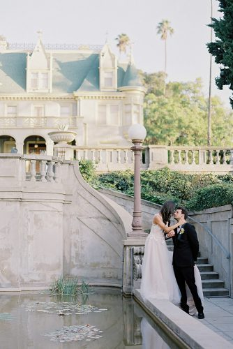besame wedding styled shoot bride in a dress with a train and the groom in the courtyard of the castle in the italian style near water carrie king photographer