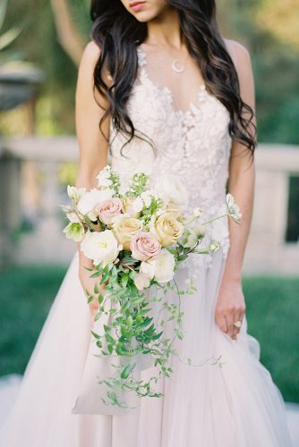 besame wedding styled shoot bride in lace dress holding a cascading bouquet with peach black pink roses and greenery carrie king photographer