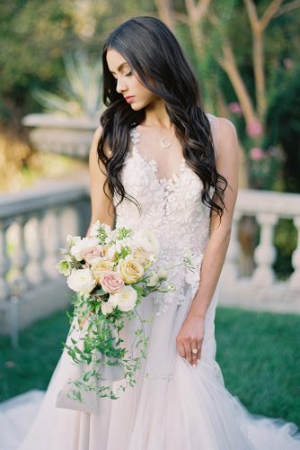 besame wedding styled shoot bride with dark loose curls in lace dress with cascading peach pink white roses bouquet with carrie king photographer