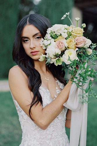 besame wedding styled shoot bride with dark loose hair holding a cascading bouquet with peach black pink roses and greenery carrie king photographer
