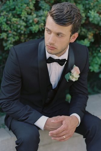 besame wedding styled shoot groom with a butterfly in a black suit with a boutonniere of roses carrie king photographer