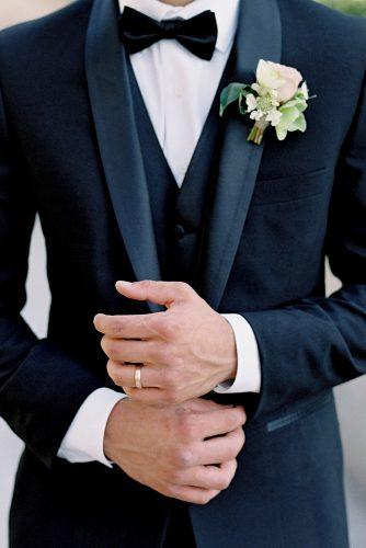 besame wedding styled shoot groom with a butterfly in a black suit with a waistcoat and a buttonhole of roses on his finger a simple gold ring carrie king photographer