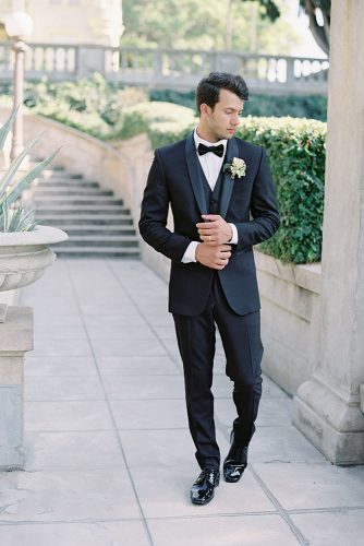 besame wedding styled shoot groom with a butterfly in a black suit with a waistcoat in black lackered leather shoes and a buttonhole of roses carrie king photographer