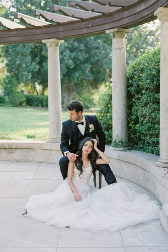 besame wedding styled shoot romantic photography bride with dark loose curls and groom with boutonniere sit near the columns carrie king photographer