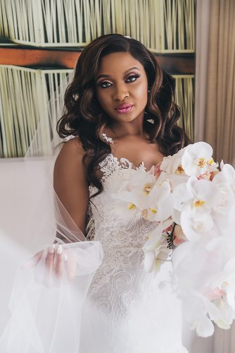 real wedding photography black bride makeup with long lashes pink lips loose curls lace dress white orchid bouquet stanlo photography