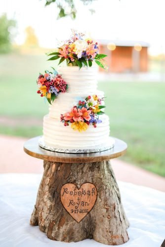 small rustic wedding cakes buttercream white with pastel flowers on wooden stand shara jo photography