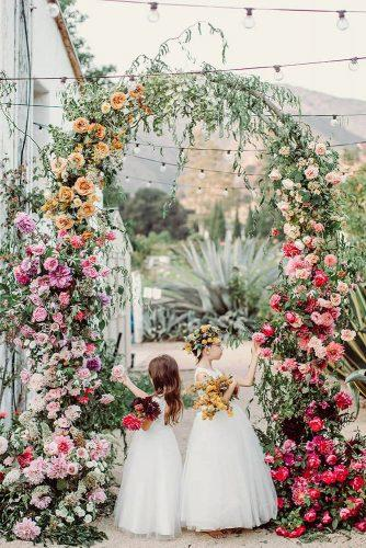 wedding decor 2019 arch with greenery and bright flowers flowergirls jonachristinaphoto