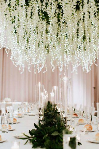 wedding decor 2019 hanging floral installations white flowers and lighting garland above table with candles and greenery tablerunner haley ringo photography