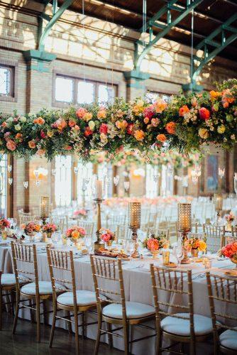 wedding decor 2019 orange and coral flowers and greenery hanging above table with tall candle centerpieces tim tab studios